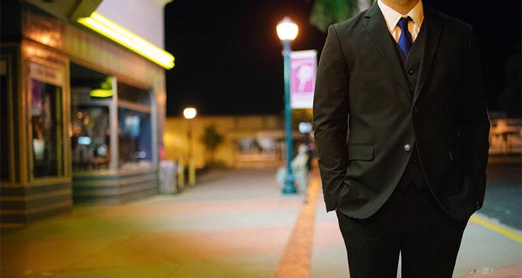夜の街に立っているスーツの男性