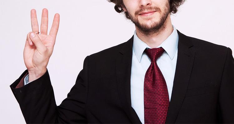 三本指を立てるスーツの男性