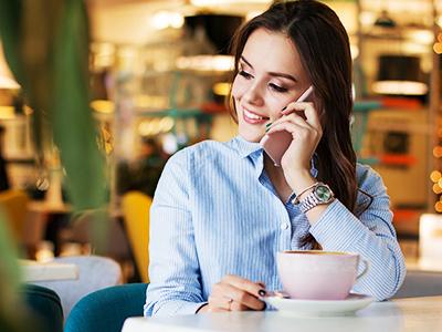 カフェで電話をする大人の女性