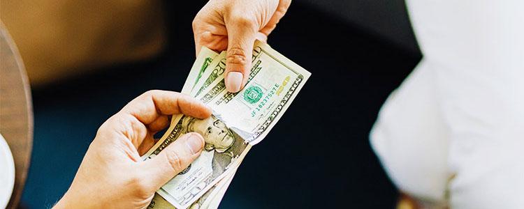 女性にお金を渡す男性の手元