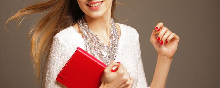 赤いノートを持った笑顔の女性