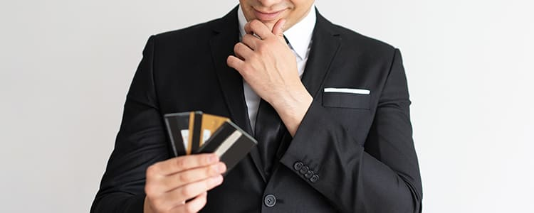 クレジットカードを見つめながら微笑む男