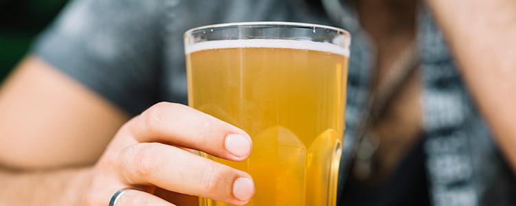 結婚指輪をしている男性がビールを飲んでいる