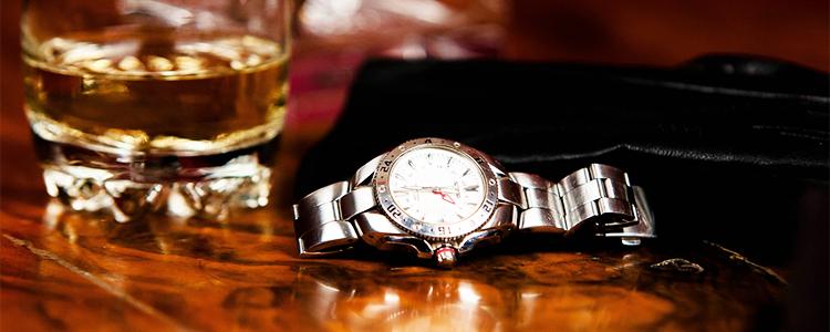 テーブルの上の腕時計とウイスキー